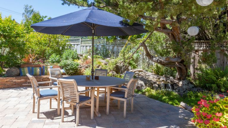 backyard patio ideas with outdoor dining table and parasol