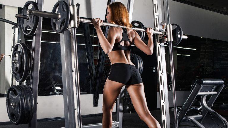 Woman starting a pulling split squat using a Smith machine