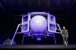 Blue Origin founder Jeff Bezos with a mockup of the company's Blue Moon robotic lunar lander during its unveiling on May 9, 2019. On Oct. 22, Bezos unveiled new partners for a lander to carry NASA astronauts.