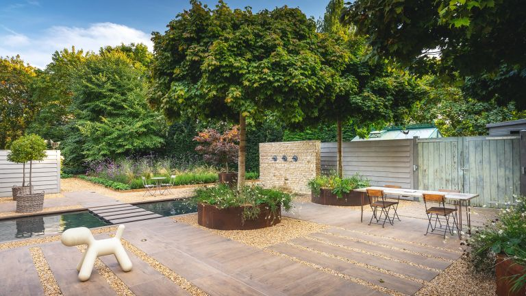 south-facing garden ideas showing paved patio, gravel paths and a water feature