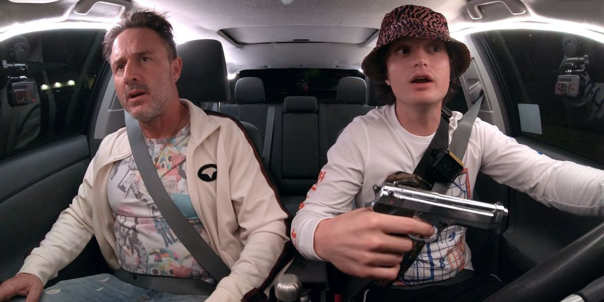 Spree David Arquette and Joe Keery talking while a gun is present