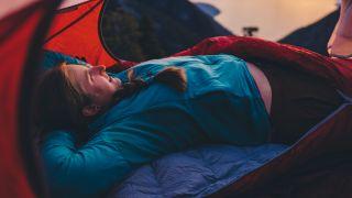 A woman lying on a 2-season sleeping bag