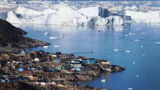 Ice floats past the village of Ilulissat in Greenland.