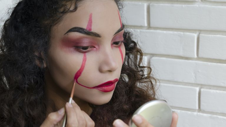 Woman Putting On Evil Clown Makeup for Halloween - stock photo