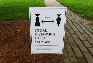 A lawn sign asking visitors to Williamsburg, Virginia to stay 6 feet apart during a tour.