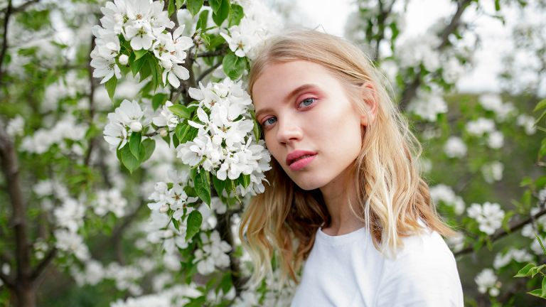 Blond haired young woman among white blossoms - stock photo