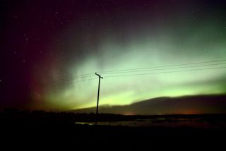 lonely power line silhouetted against aurora in sky