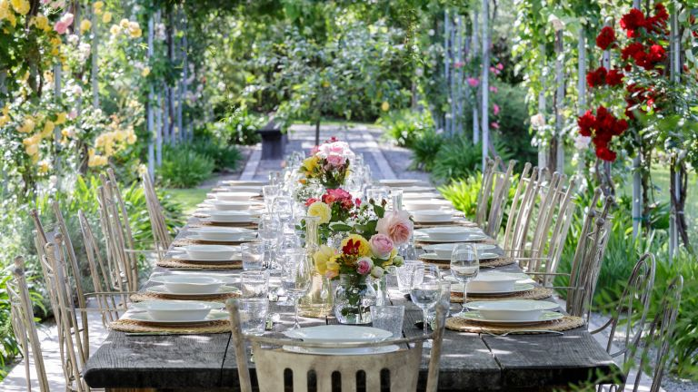 table setting beneath pergola for backyard wedding ideas