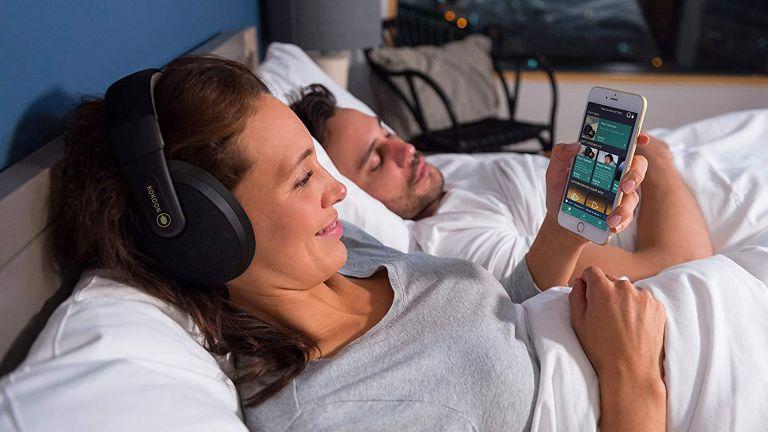 best sleep headphones: Woman wearing Kokoon Sleep Headphones in bed