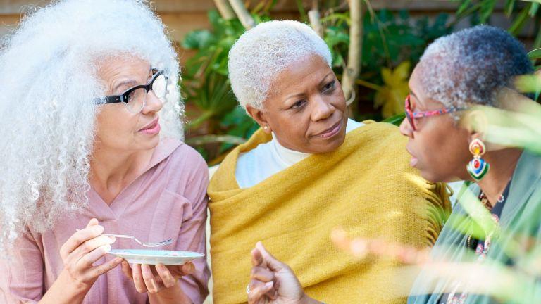 three women chatting in a garden