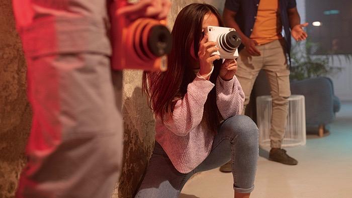 Young woman using a Fujifilm Instax Square SQ1 camera