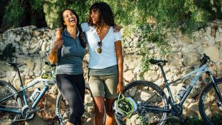 Cycling on your period: Two women are standing next to their bikes, holding their helmets and laughing together