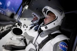 Demo-2 crewmates Bob Behnken (left) and Doug Hurley take part in a full simulation of launch and docking of SpaceX's Crew Dragon spacecraft inside a flight simulator. While learning how to fly the capsule, the two astronauts made suggestions to SpaceX but avoided customizing the Dragon to fit their preferences.