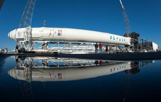 SpaceX's Falcon 9 rocket and Dragon capsule roll out from the hangar for the CRS-2 launch.