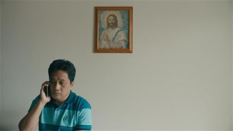 Joshua (Rogelio Balgatas) on the phone, under a painting of Jesus