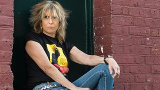 Close-up colour portrait of Chrissie Hynde sitting in a doorway in a red-brick wall