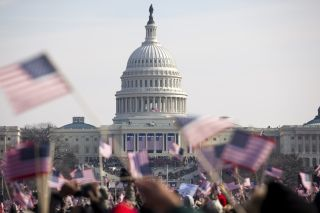 Photo of the U.S. Capitol behind of a crowd waving American flags at President Obama's inauguration on Jan. 20, 2009.