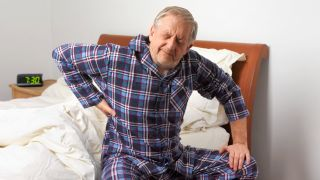 Why do I have back pain? Man struggling to get out of bed and clutching his lower back