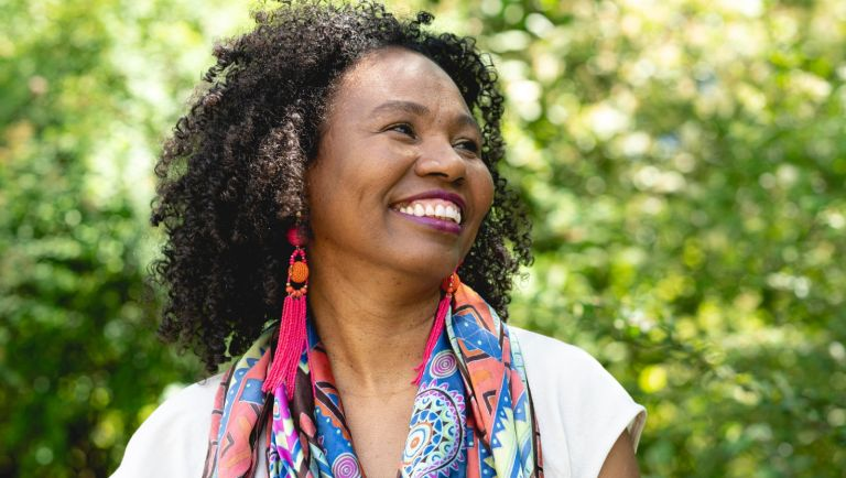 Portrait of a laughing, dark-skinned woman with curly hair and colourful scarf, Germany - stock photo