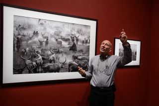 50 best photographers ever: Sebastiao Salgado in front of one of his pictures from Genesis