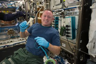 "International Space Station Commander Barry ""Butch"" Wilmore shows off a ratchet wrench made with a 3D printer aboard the orbiting lab. The wrench and other parts will return to Earth for comparison with ground samples in early 2015."