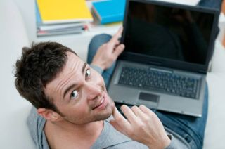 Smiling young man looking back at camera while working on laptop at home