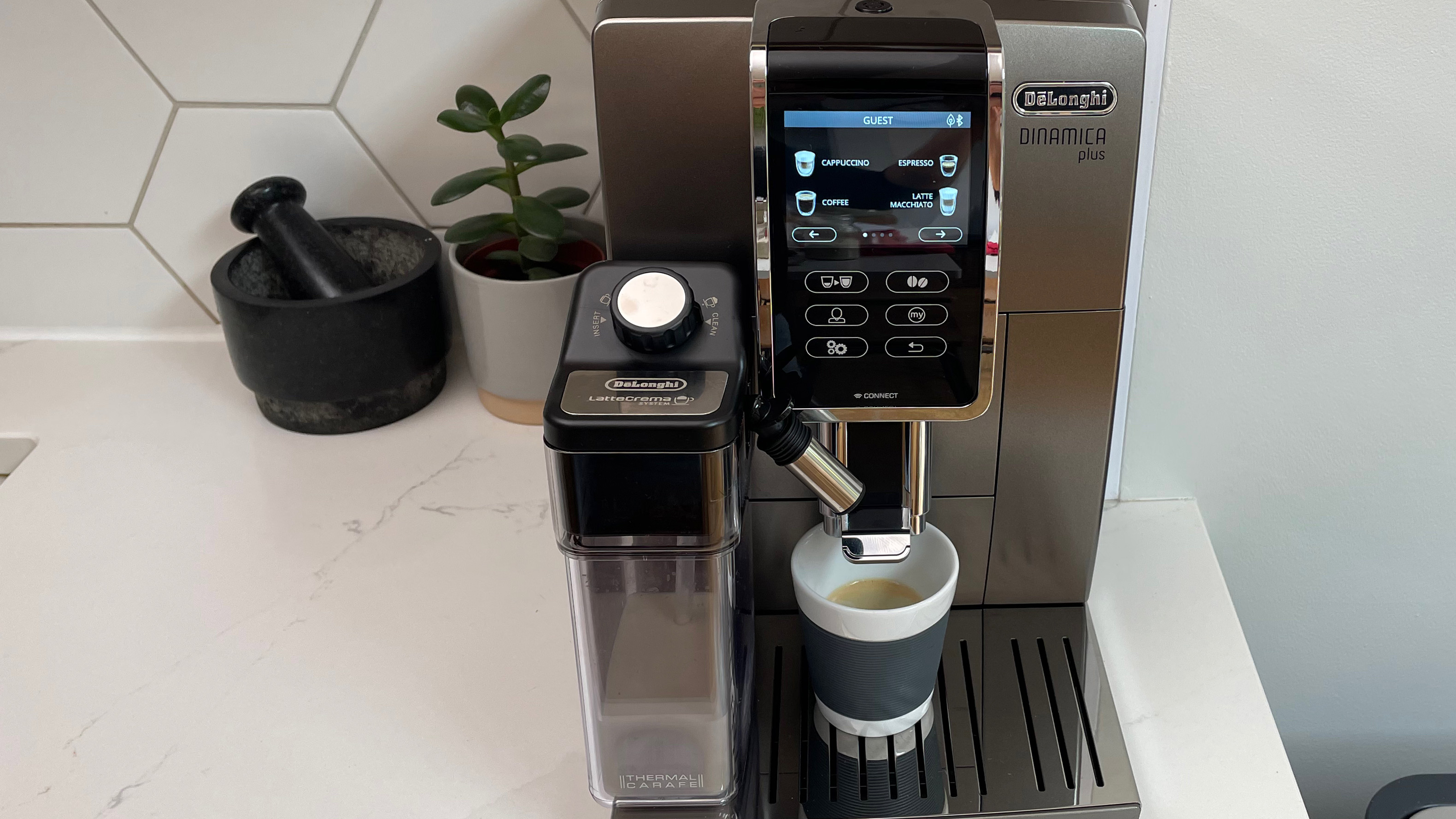 De'Longhi Dinamica Plus on a kitchen countertop with milk in the frofther, ready to pour an espresso