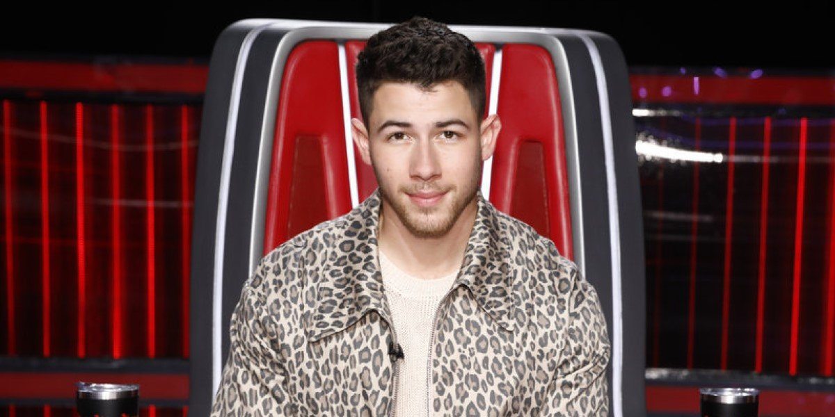 nick jonas sitting in his chair on the voice