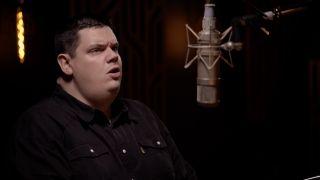 Peter Jones singing into a microphone