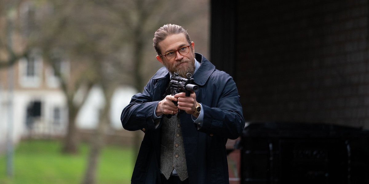 Ray (Charlie Hunnam) points a gun at an off-screen figure in 'The Gentlemen.'