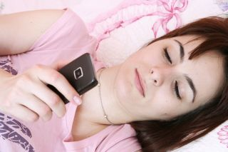 A woman uses her cell phone in bed.