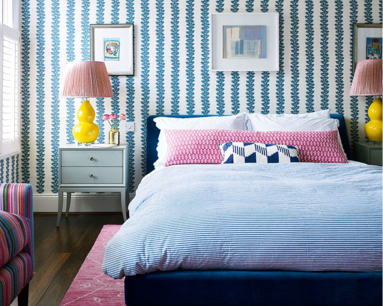 How to choose the best bedroom colors, in a blue and white scheme with yellow and pink accents and striped wallpaper.