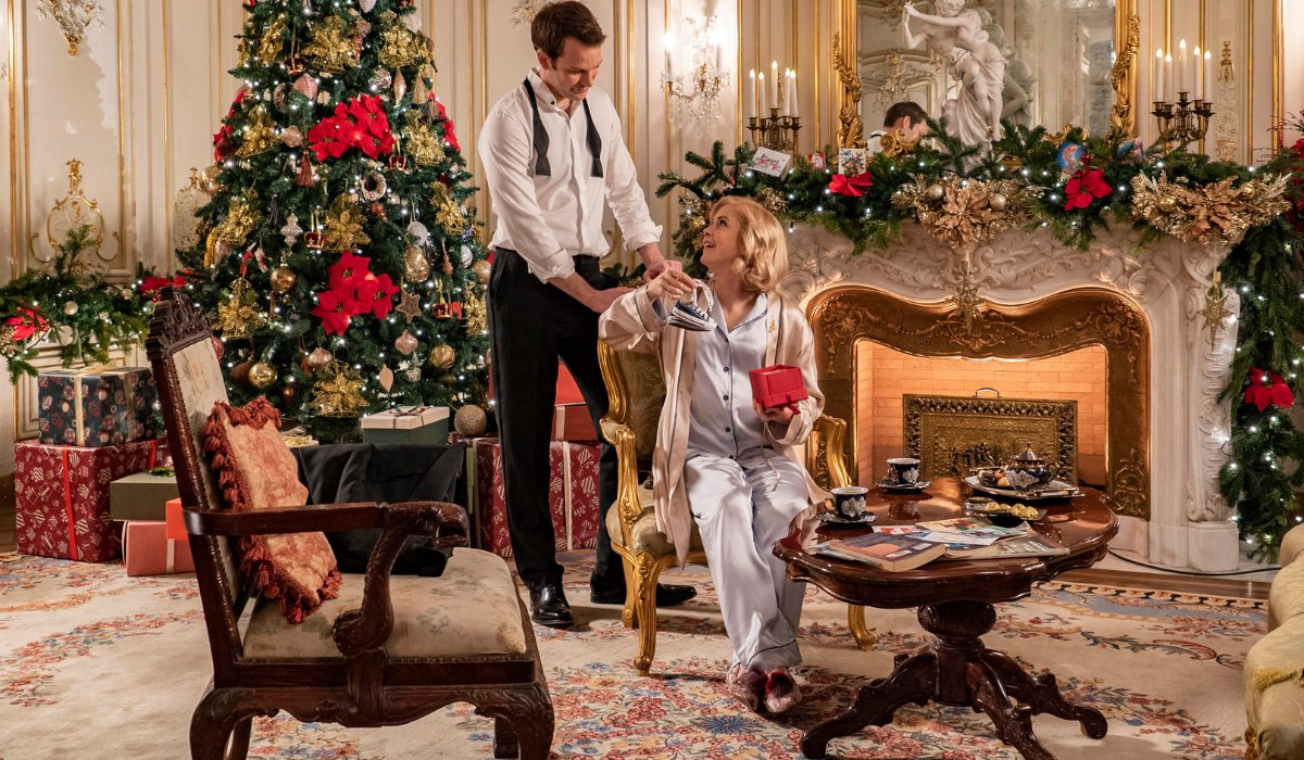 A Christmas Prince: The Royal Baby the prince and princess marvel over baby shoes by the fire