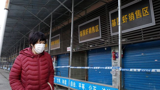 A woman walks in front of a closed seafood market in Wuhan, China. Officials believe the market is linked with an outbreak of pneumonia caused by a new virus.