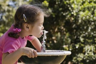 Young girl drinking water from a water fountain.