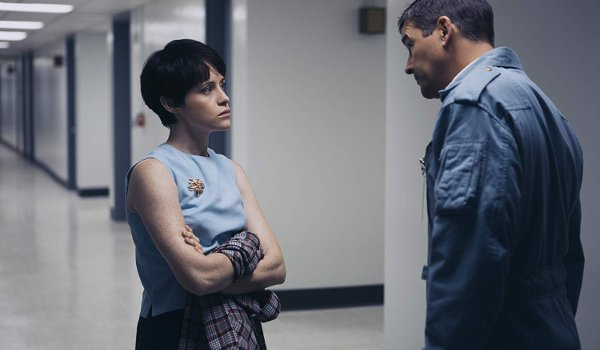 First Man Claire Foy glares at Kyle Chandler, arms crossed, in a hallway
