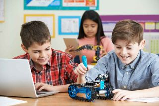 Two boys and a girl working with robots in the classroom