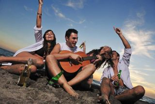 happy young friends group have fun and celebrate on the beach with a guitar and beer
