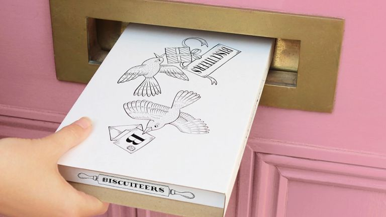 Valentine's Day gifts: Biscuiteers box being posted through letterbox of pink dor