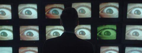 Mehmet stars at a wall of TVs displaying eyeballs.