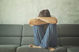 A man sits on a couch, crying and hiding his face