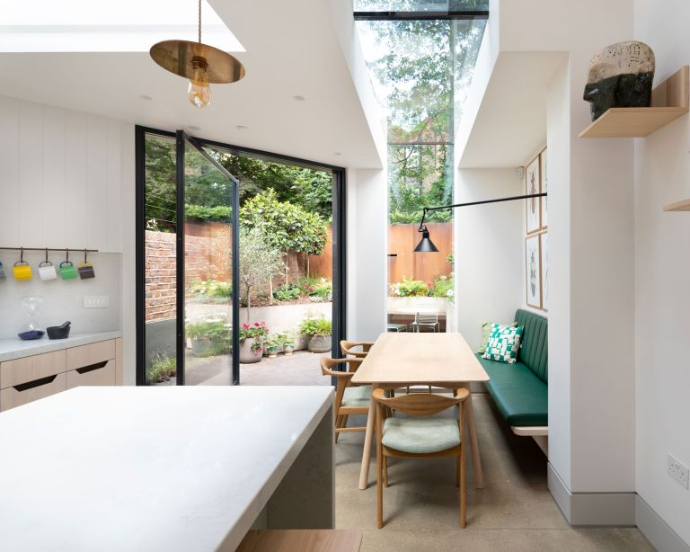 An example of installing patio doors showing a kitchen with a glass roof, wooden dining table and glass patio doors