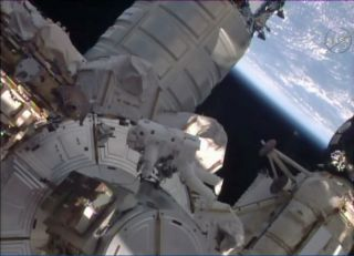 Astronaut Tim Kopra works near the massive Cygnus supply craft docked to the outside of the International Space Station.