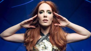 Epica's Simone Simons with her hands touching the sides of her head