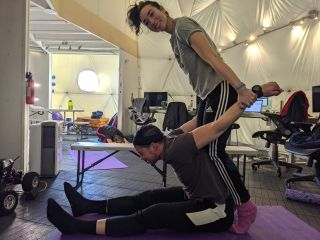 Valoria 2 crewmembers doing rigorous stretching post-handstand training at the HI-SEAS research station during a simulated Mars mission.