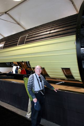 Phil Pressel, designer of the KH-9 HEXAGON's 'optical bar' panoramic camera system, poses in front of the massive 60-foot long spy satellite at the Smithsonian National Air & Space Museum's Udvar-Hazy Center on Sept. 17, 2011. The National Reconnaissance