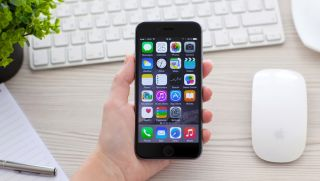 A hand holding a brand-new iPhone 6 over an Apple Magic Mouse and iMac keyboard.