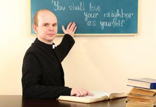 priest teaching sunday school at chalkboard