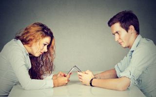 A man and woman sit across table from each other, each looking at their smartphone.