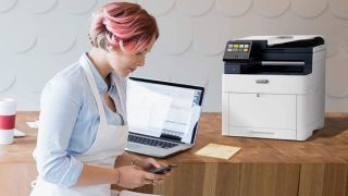 best Mac printer: Woman with laptop and Xerox WorkCentre 6515dni printer on desk
